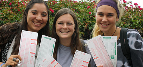 Three students holding scantrons